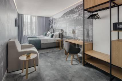 Moderní interiér apartmánu s dvěma oddělenými postelemi, psacím stolem a drobným posezením.